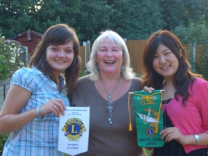 Youth Exchange visitors Ema and Yumiko presenting their home clubs' bannerettes to Lion President Helen Summer 2009